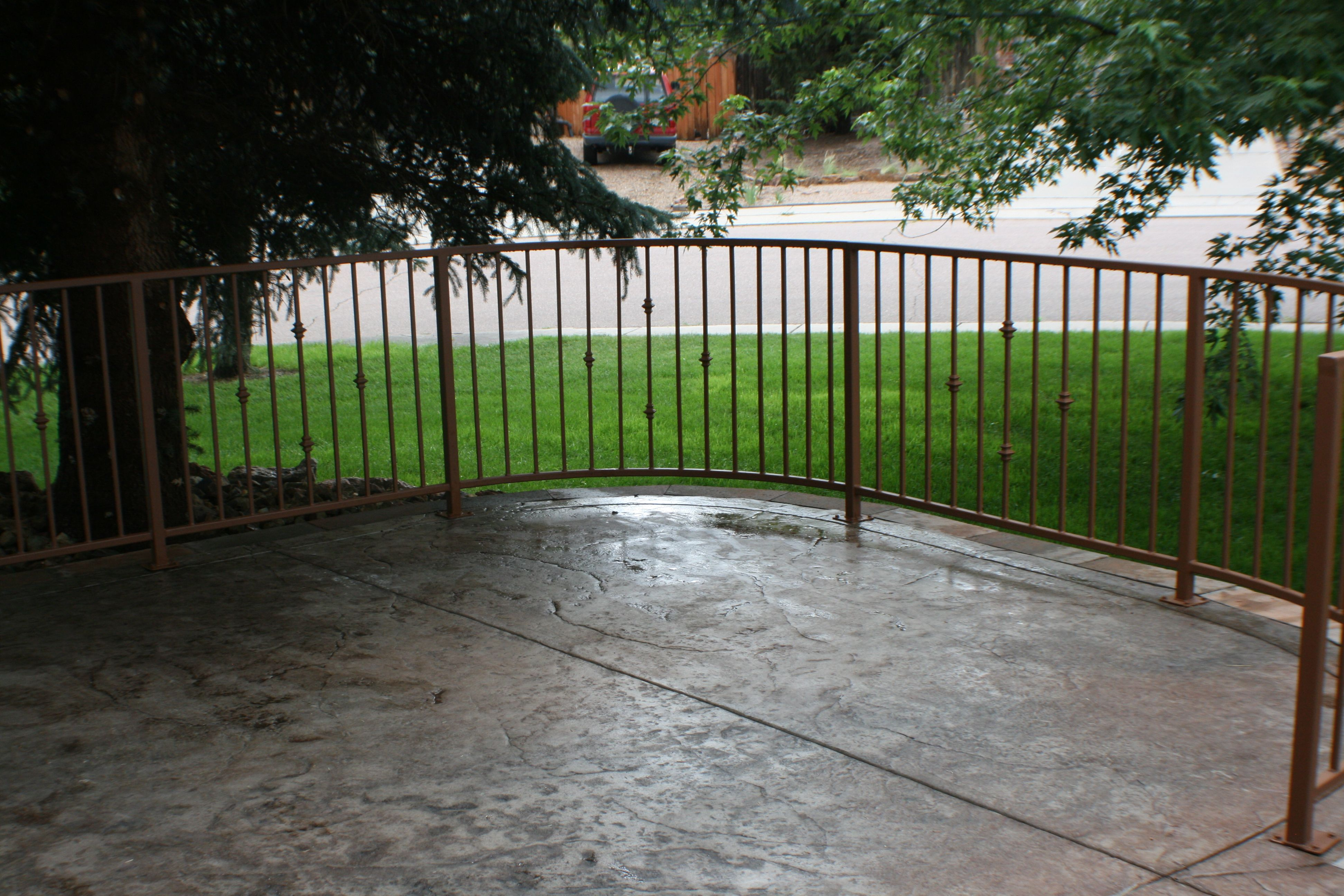Patio With Colored Stamped Concrete And Rod Iron Railing