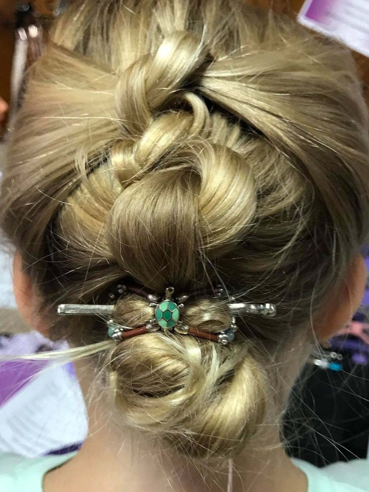 Cute little green turtle flexi clip secures a french knots hairstyle