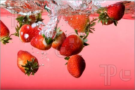 Picture of Strawberries falling in red water with splash and bubbles
