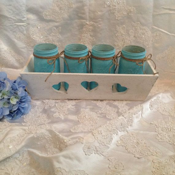Four Mason Ball Jars in Wood Crate. This wood crate was painted a soft white and then given a shabby chic distressed finish. It has three heart cut outs in the front. The jars are one quart Ball mason jars and have been primed in white and then painted turquoise. They were then given a shabby chic distressed finish to show the lettering of the jar. They are wax sealed to protect the finish. They are wrapped in jute twine at the top. The vases can hold water if needed. This set would make a…