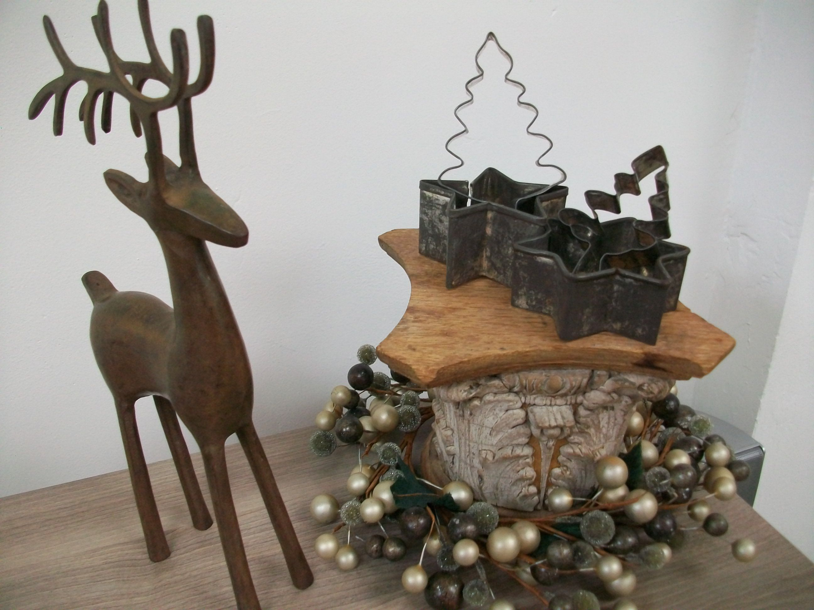 Reindeer, mini green/gold berry wreath, salvaged wooden capital, vintage tree & star cookie cutters.