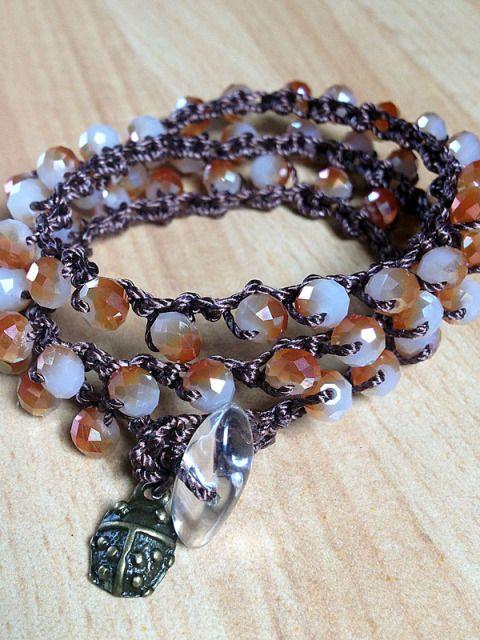 Questo Luccichino può essere indossato come una collana di 50 cm o come un braccialetto, avvolgendolo al polso con 3 giri.  Realizzato con mezzi cristalli bianchi/arancio e resistente filo di nylon color marrone mediante la tecnica crochet.