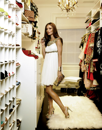 A sheepskin rug, Lucite stool, and chandelier dress up an otherwise basic, white laminate shelving system in one of Georgina Chapman's three closets #closet #Georgina_Chapman #Marchesa
