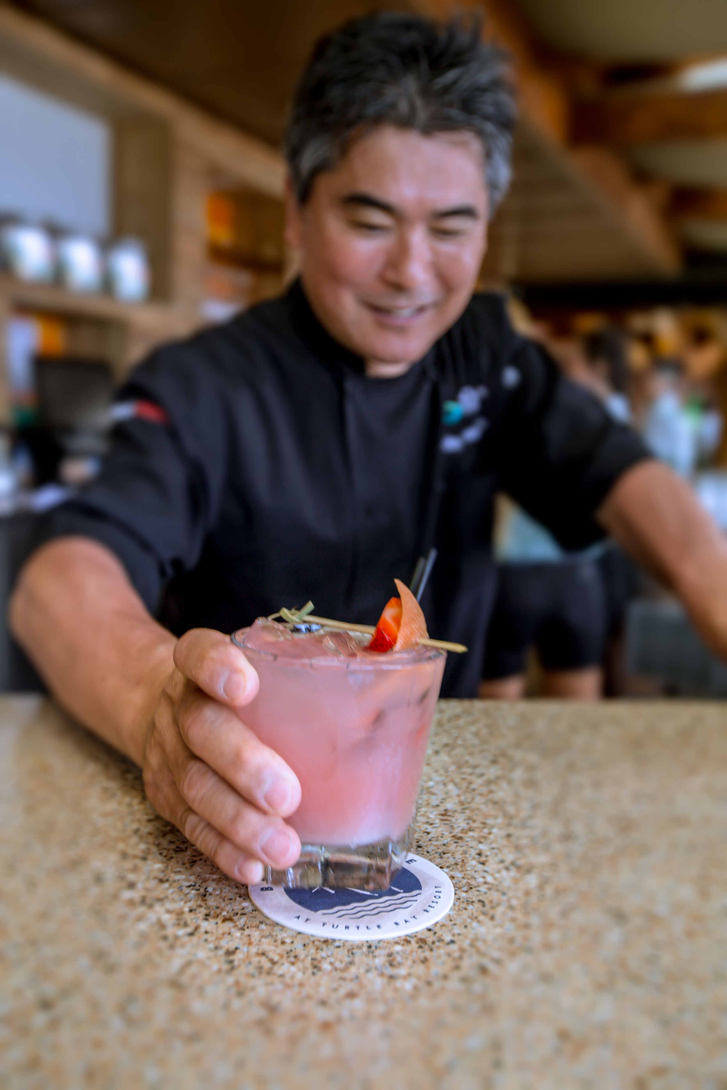 Chef Roy Yamaguchi serving up a signature #RoysBeachHouse cocktail. Wave Watching | Kai Vodka, Lemon Juice, housemade Lavender syrup, strawberry puree & coconut water.