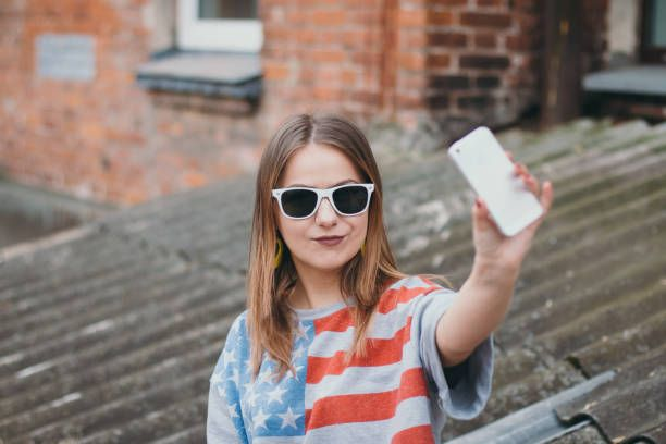 hippest girl in an old courtyard with a phone makes a selfie