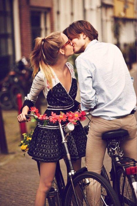 hombre en una bicicleta besando a una chica que también está en bicicleta