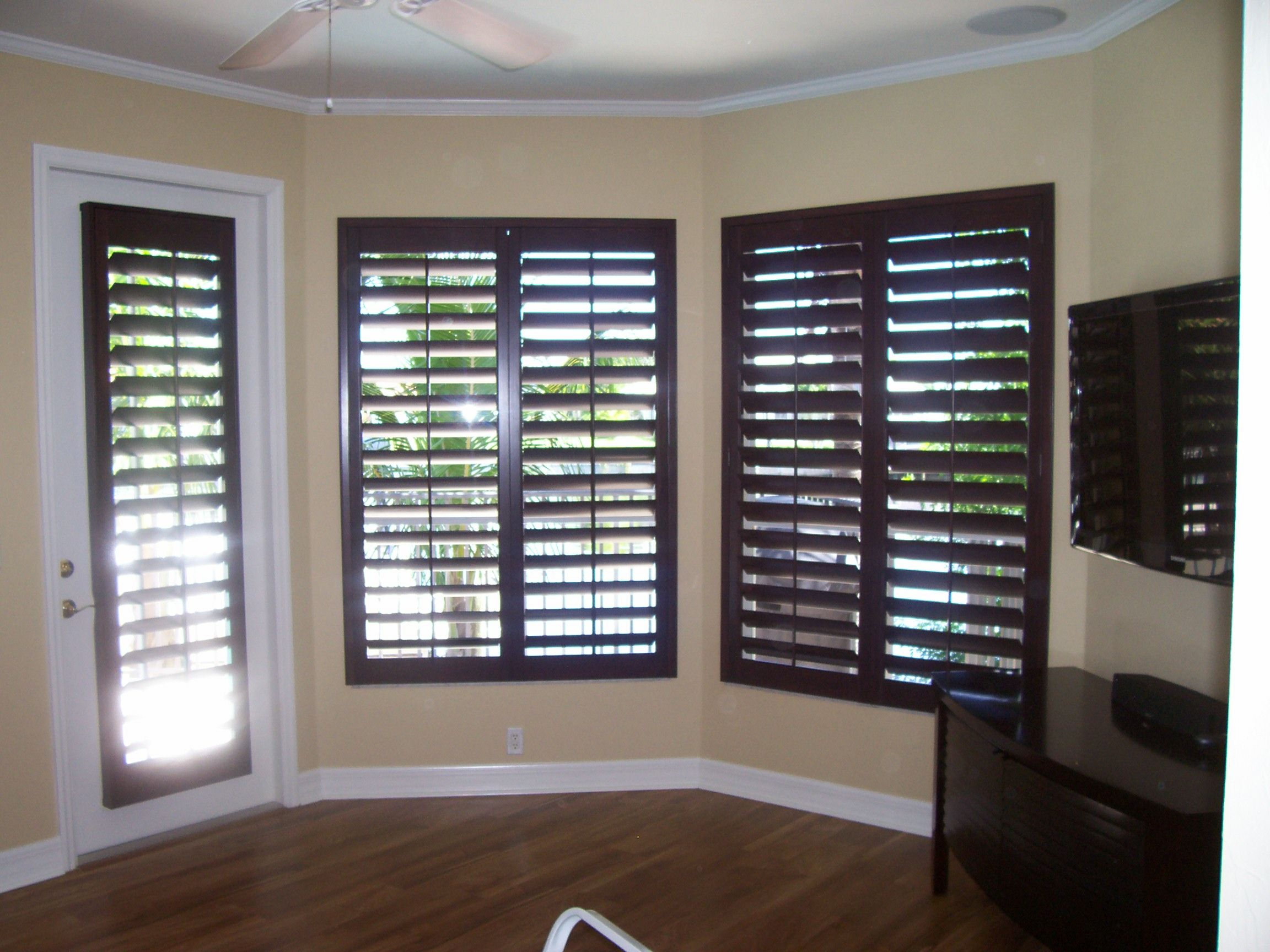 Dark Wood Plantation Shutters With Yellow Brown Walls And White Molding Window Treatments