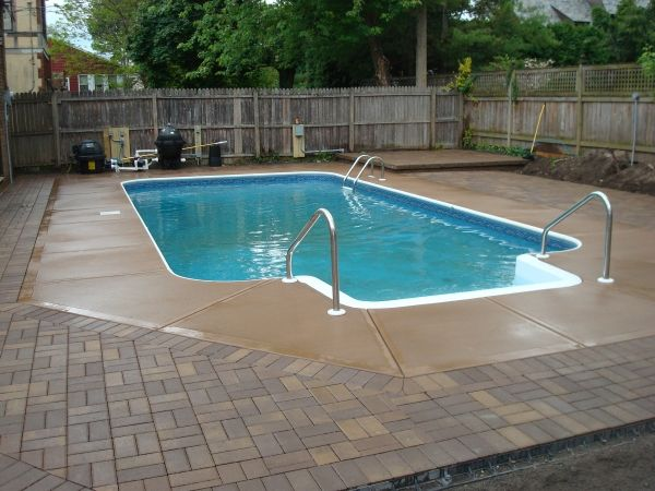 Pool deck with brown concrete and pavers california for Best pavers for pool deck