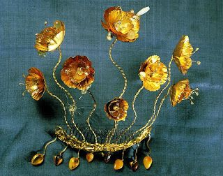 Queen Margrethe of Denmark Golden Poppies ~  Made by Griegst in 1976 of 21k gold with aquamarines, diamonds, moonstones, opals, and pearls The poppies are detachable and can be worn separately. Each flower has baroque pearls inside and 4 diamond-tipped stamens. The design is a very literal translation of a garden flower, including moonstones and aquamarines on the leaves to represent dewdrops and insects. Supposedly there are tiny lights, to illuminate the flowers.