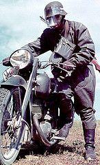 A Wehrmacht man mounts a motorbike.
