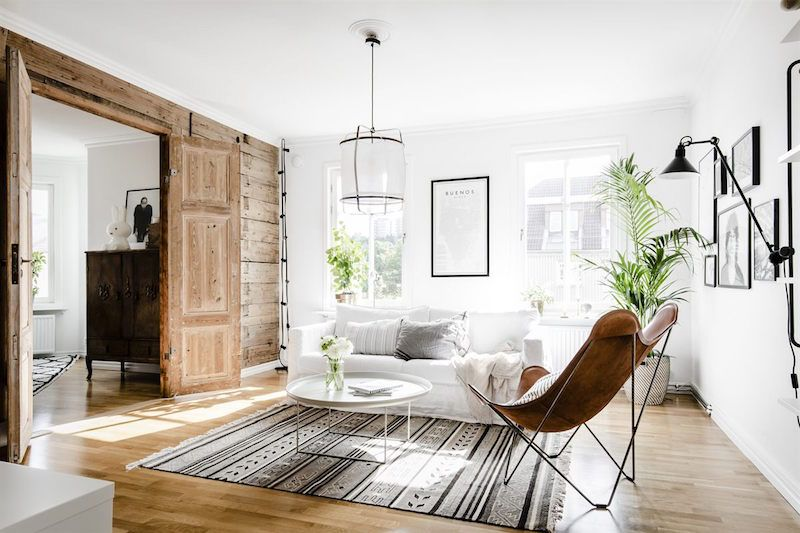 distressed wood features to contrast with the white walls in this apartment in sweden