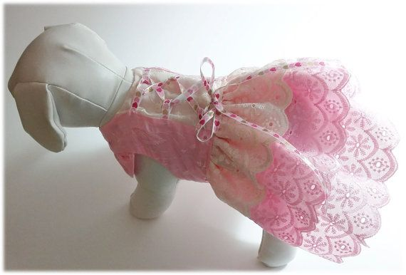 This adorable, hand sewn dog dress is made of pink and cream eyelet cotton fabric. The skirt has two layers of pink eyelet with the top layer a cream eyelet. The top is pink eyelet with the center being cream with heart ribbon laced down the middle. Please make sure your pet fits within these measurements  Neck: 7-8 in. Girth: 11-12 in. Length: 9.5 in.  - Hand or spot wash, light iron - Velcros at neck and waist for easy adjustment - Fits dogs approx 3.5-4 lbs - Smoke-free home  I am not a…