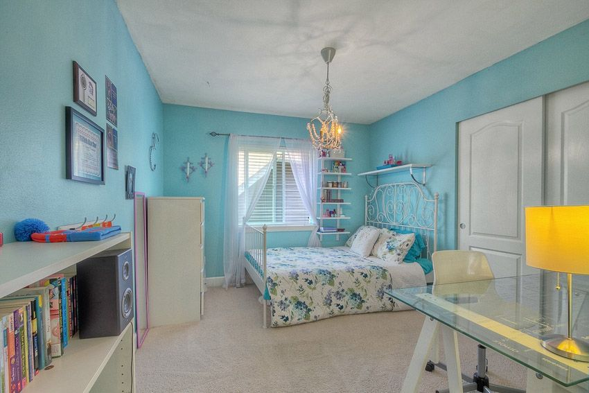 Girls bedroom with white furniture, chandelier and blue painted walls.