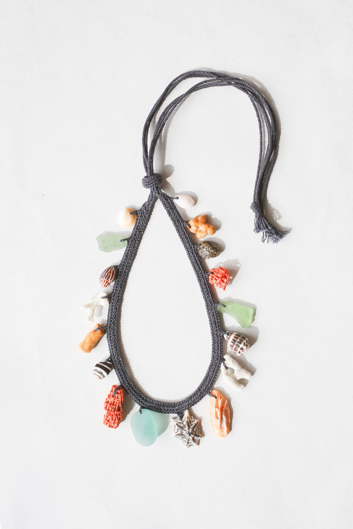 Plaited cotton necklace with shells, glass and coral