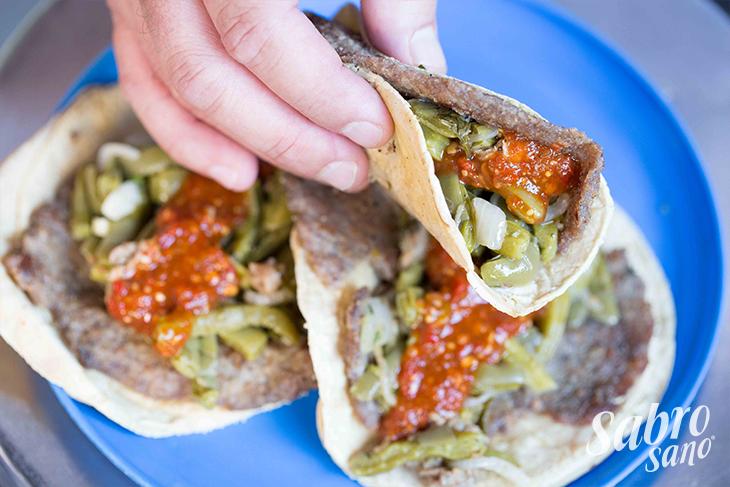 TACO DE MILANESA -CDMX- Una combinación de dos platillos tradicionales. La milanesa de res empanizada que suele acompañarse con nopales guisados en cebolla, se combina con la tortilla para crear un taco único. La costra crujiente de la milanesa le da ese extra a cada mordida.  • Tortilla de Maíz • Milanesa de Res Empanizada • Nopales Guisados con Cebolla • Salsa Roja