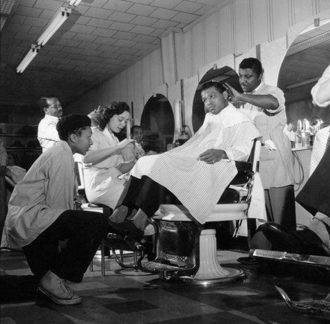 Sugar Ray Robinson inside his Harlem barbershop in 1951, having his hair done by Rogers Simon.