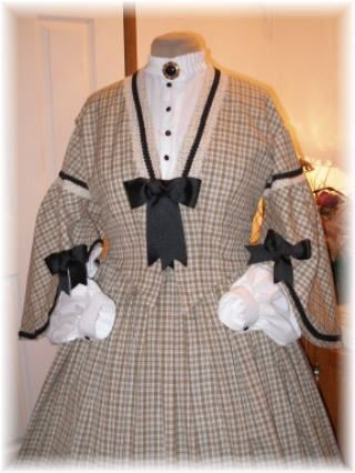 SomeWear In Time Design  Ladies Civil War Ensemble  Boned and Lined Oatmeal Brown and black Cotton woven plaid bodice with crochet cotton trim, black grosgrain ribbon trim and matching bows. Sleeves feature exaggerated lower bell.  White muslin tucker with black jet buttons and self collar with brooch. White batiste undersleeves with tailored buttoned cuffs.  Full cartridge pleated skirt with hook and eye waistband.  $450  SOLD