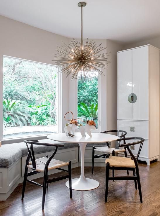 An Arteriors Zanadoo Chandelier Hangs Over An Ikea Docksta Table Seating  Hans Wegner Wishbone Chairs And A White Dining Bench Placed Under A Bay Wiu2026