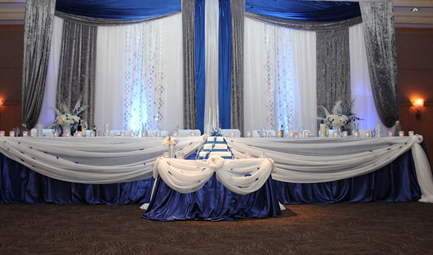 Blue, Silver, And White Wedding Decorations. I Love The Blue Petals In The  White Drapes Decor.