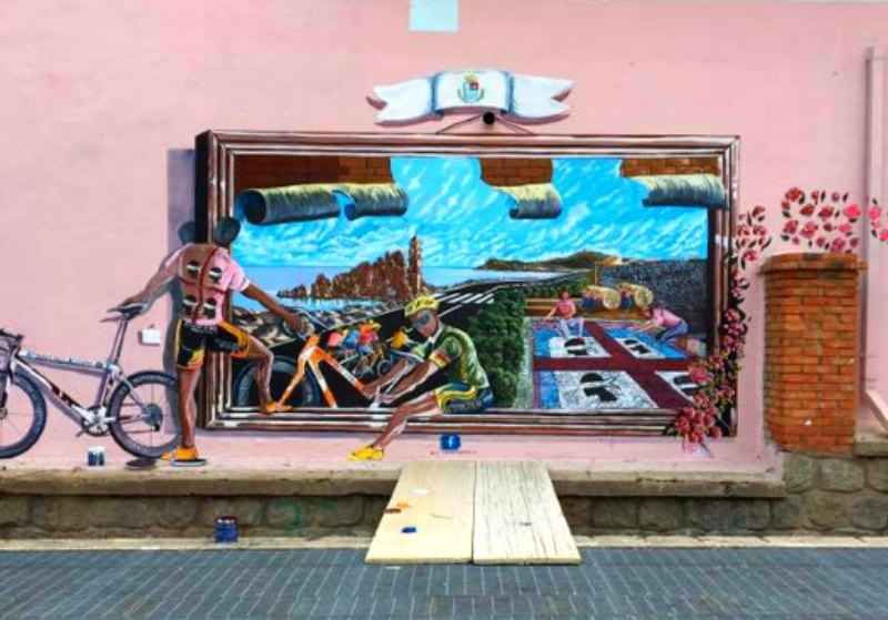 Giro d'Italia: intervista a Franco Mascia, autore del murale dedicato a Scarponi Sarà probabilmente una delle icone più rappresentative del Giro d'Italia, edizione 2017, l'edizione numero 100. Il murale realizzato a Tortolì, in Sardegna, dedicato al paese e a Michele Scarponi, il #girod'italia #tortolì #scarponi