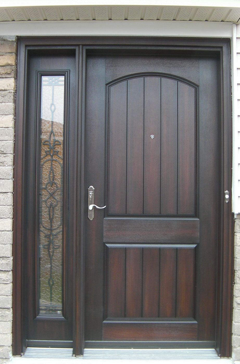 Rustic fiberglass exterior doors - Cambered Two Panel Plank Rustic Fiberglass Door With Wrought Iron Sidelite In A Light Walnut Stain