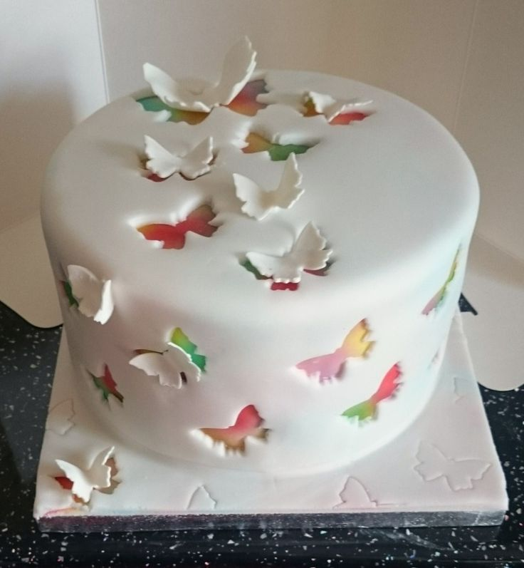 airbrushed cake covered in white fondant with butterflies cut out
