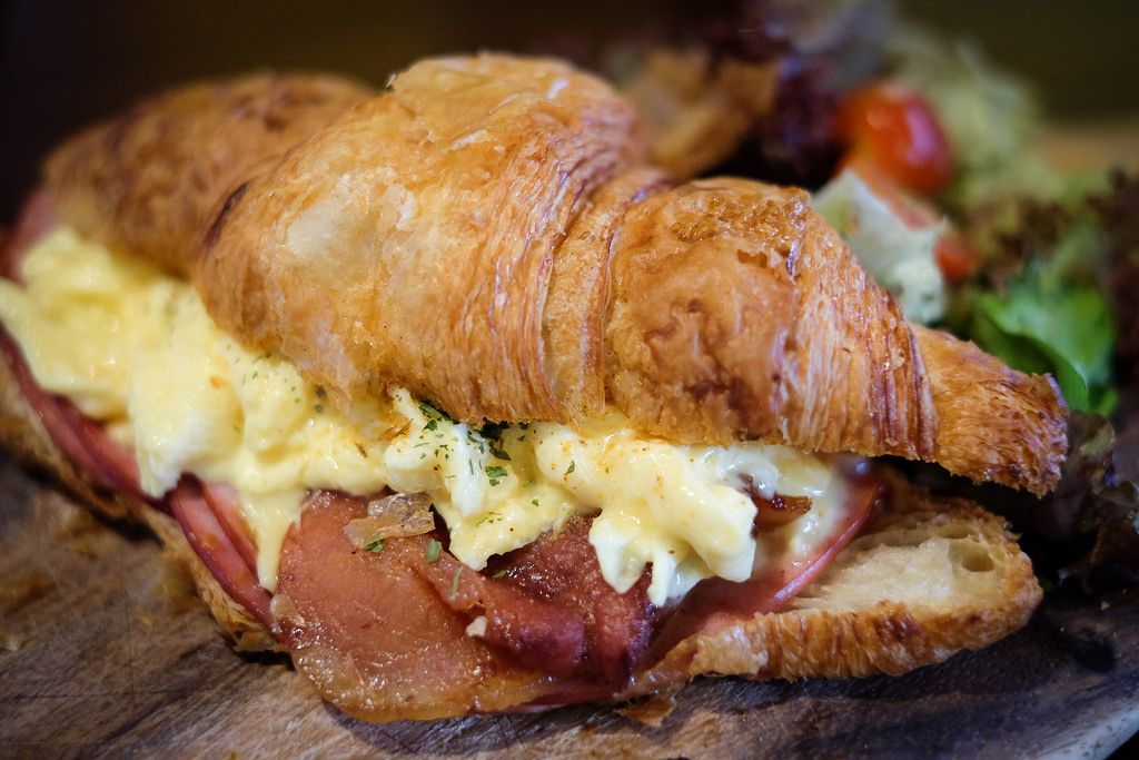 With an irresistibly flaky texture, the croissant is served with scrambled eggs, pork ham, honey bacons, cheddar cheese, cajun mayo and garden salad