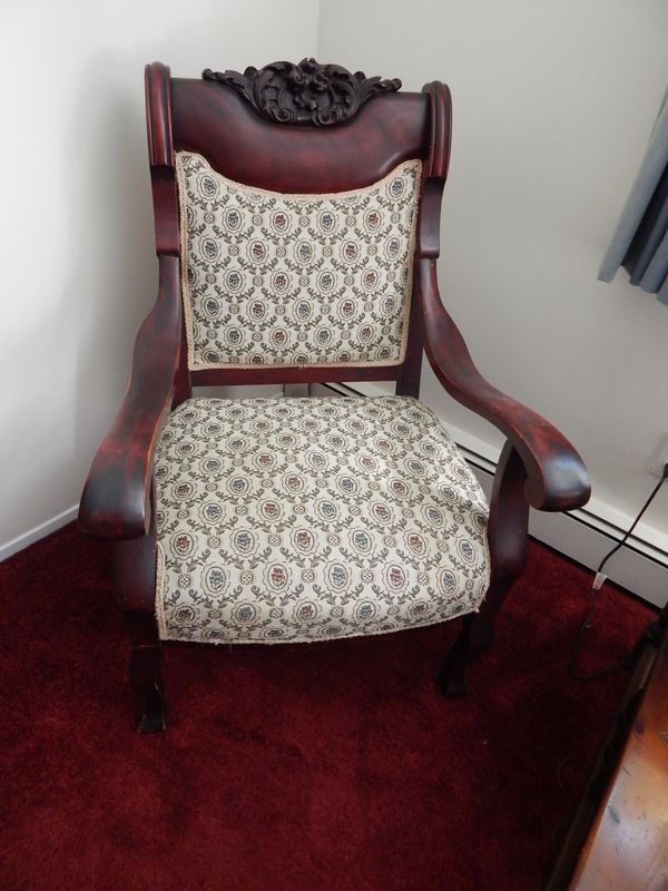 Turn-of-the-19th/20th century arm chair with a wonderful carving atop the head. It appears in very good condition