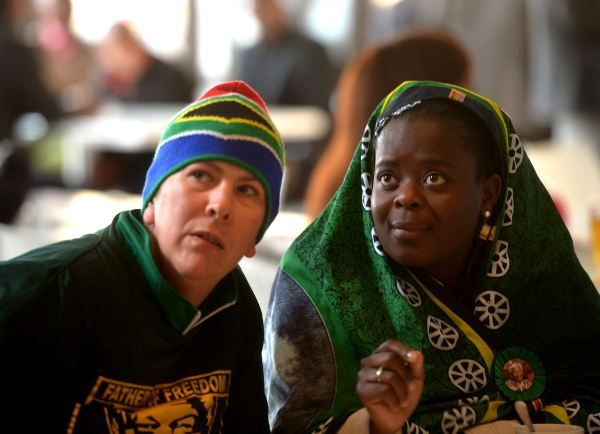 A white and a black woman watch the memorial service for Nelson Mandela on television in a bar in Soweto (AFP PHOTO / FILIPPO MONTEFORTE)