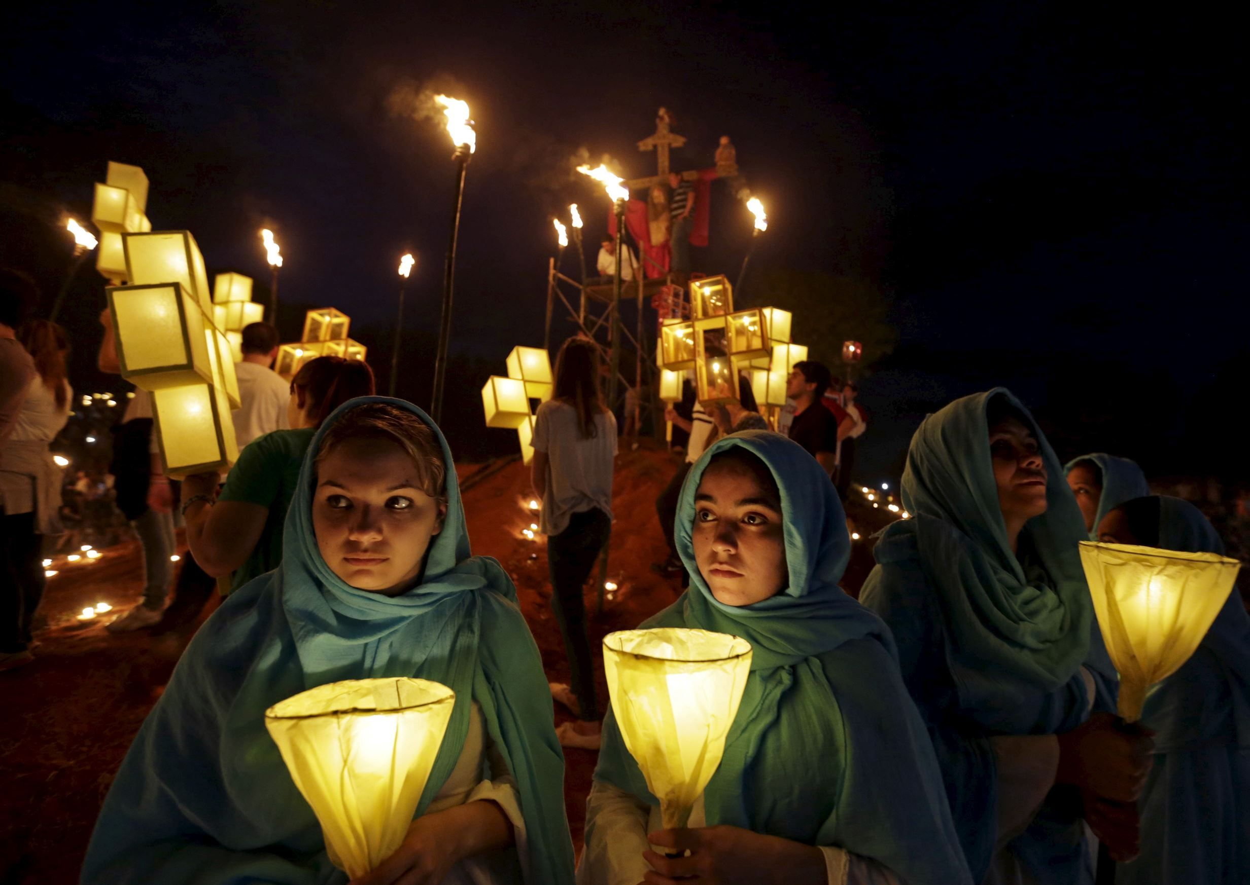 a statue of jesus christ is surrounded by women holding candles