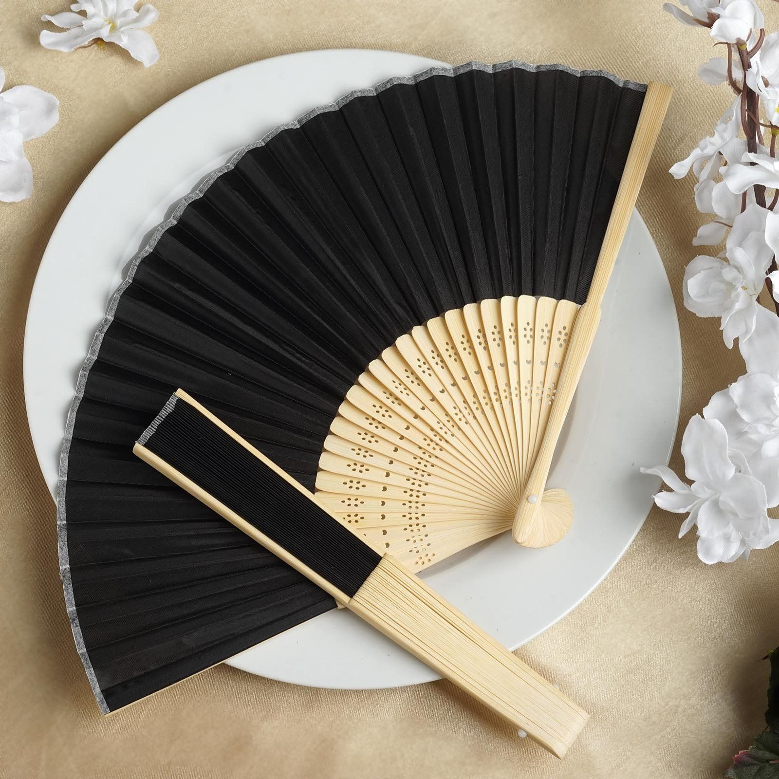 Asian Silk Folding Fans - Black | eFavorMart / Add a classical Asian touch to your wedding, or a special event by presenting your esteemed guests with this special souvenir. Our stylish silk wedding hand fan is intricately handcrafted with a bamboo structure. The framing and spines are crafted from hand-picked bamboo and durably glued with a seamless cut piece of silk to fashion this immaculate magnum opus. Give these swish fans to your respected guests and let them create the lasting memory…