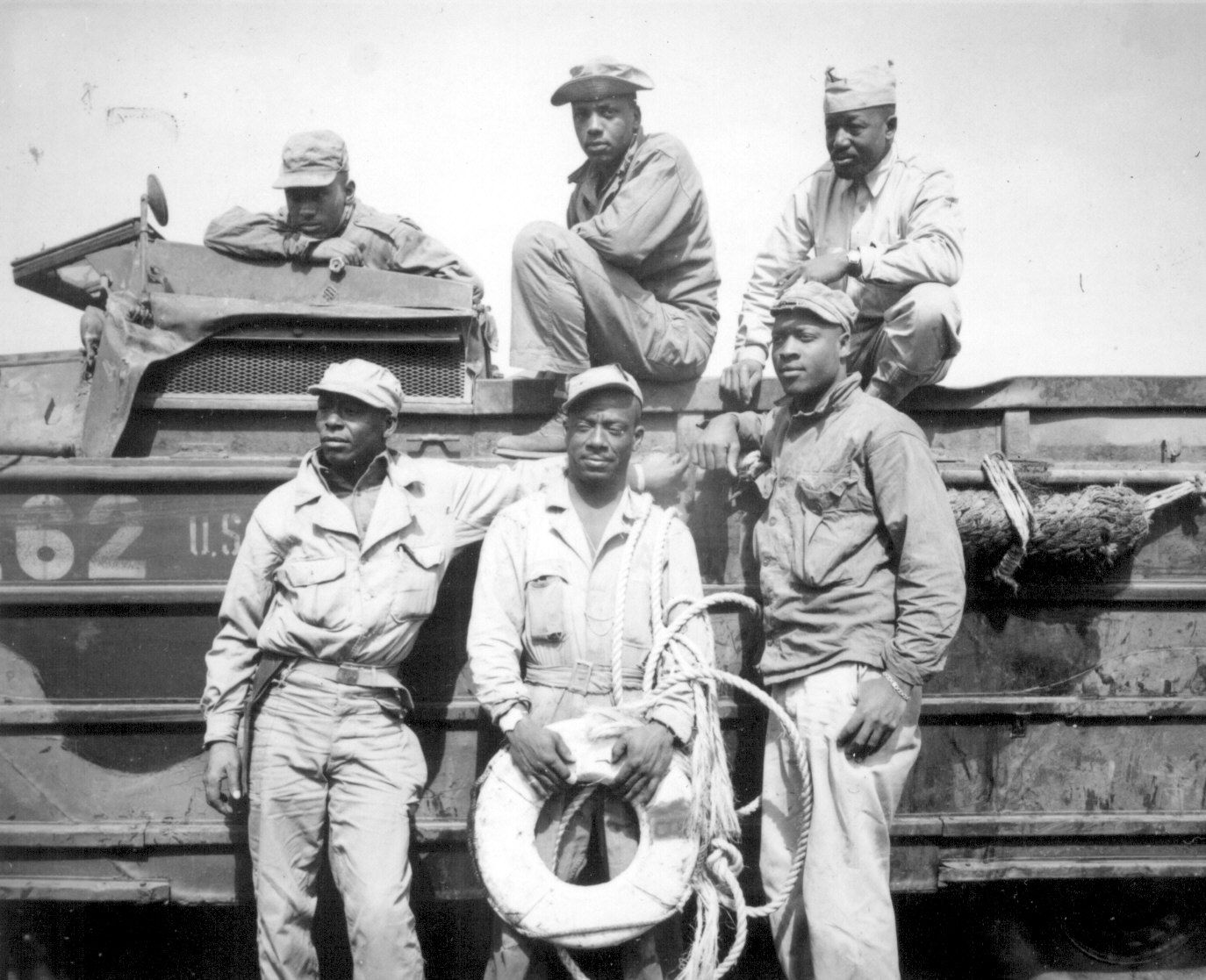 """Seeking to rescue a Marine who was drowning in the surf at Iwo Jima, this sextet of soldiers narrowly missed death themselves when their amphibian truck was swamped by heavy seas. From left to right, back row, they are T/5 L. C. Carter, Jr., Private John Bonner, Jr., Staff Sergeant Charles R. Johnson. Standing, from left to right, are T/5 A. B. Randle, T/5 Homer H. Gaines, and Private Willie Tellie."" March 11, 1945. (S/Sgt. W. H. Feen)"