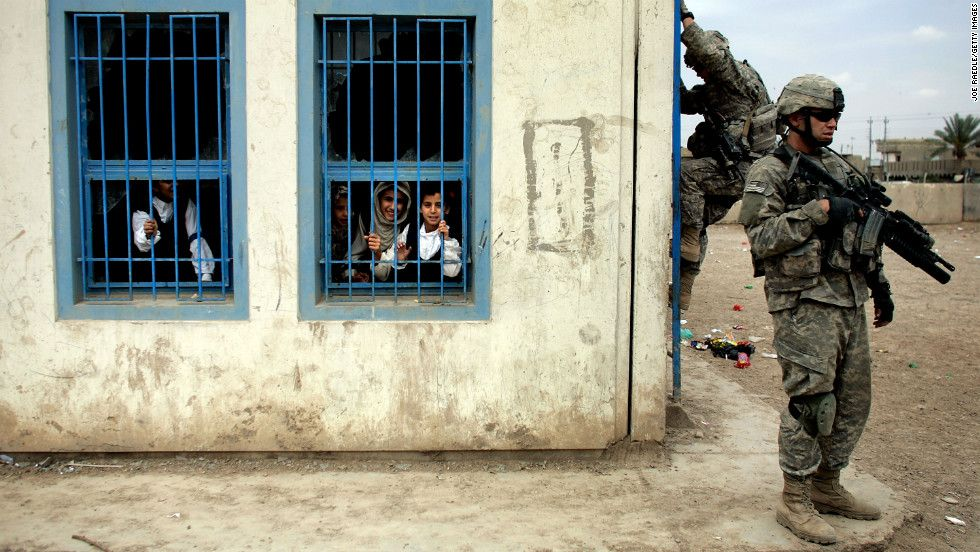 Iraqi Children Watch U S Army Soldiers Climb To The Roof Of Their School To Get A High Vantage Point In Baghdad On April 15 2007 Iraq War War Heart Of America
