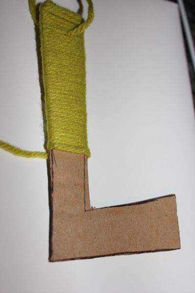 Cardboard and yarn...cheaper than buying wood letters.