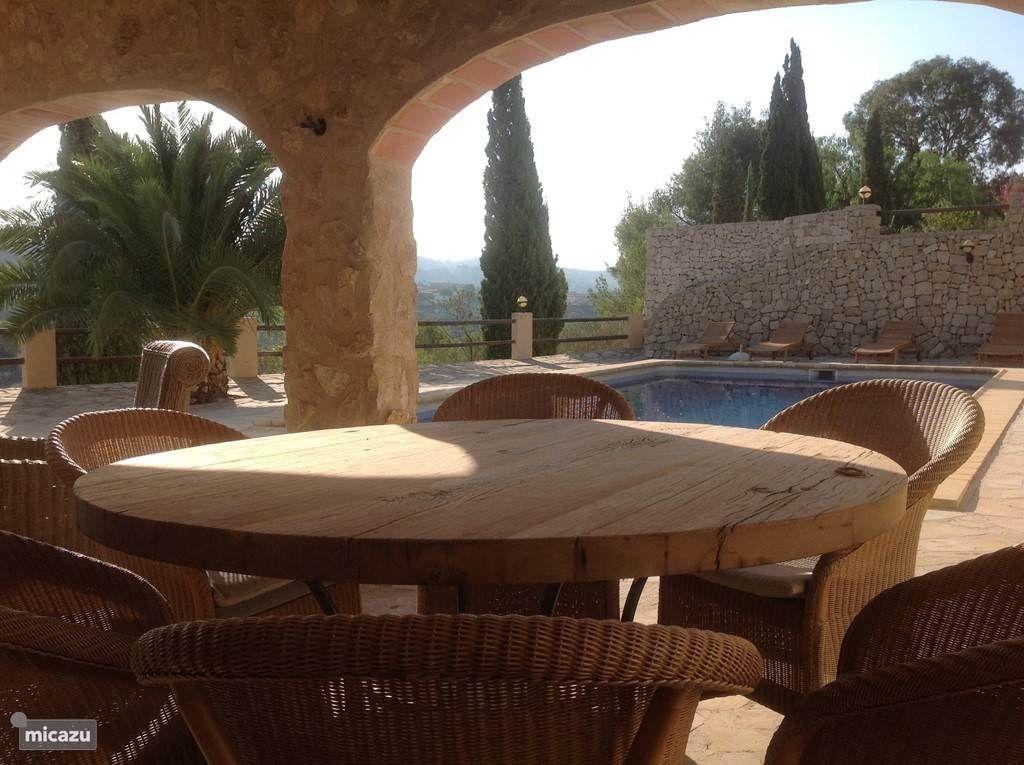Een grote ronde tafel onder de naya bij het zwembad een