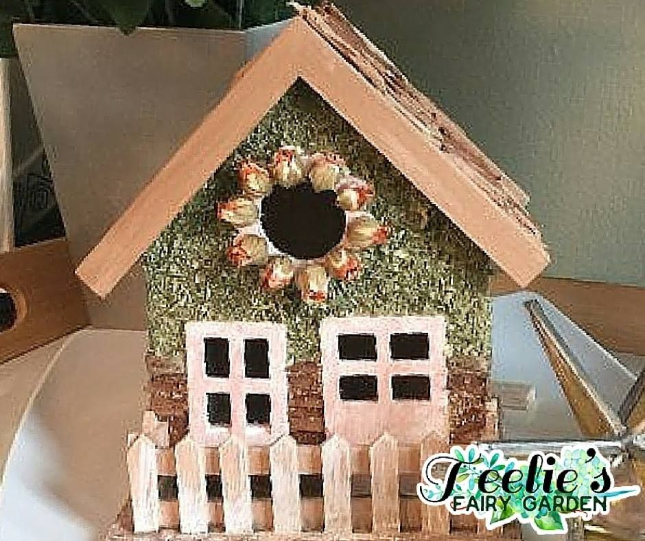 Wooden Fairy House www.teeliesfairygarden.com Bring home this beautiful wooden fairy house with a flower wreath. It's a perfect addition to your fairy garden so have it today! #fairyhouse