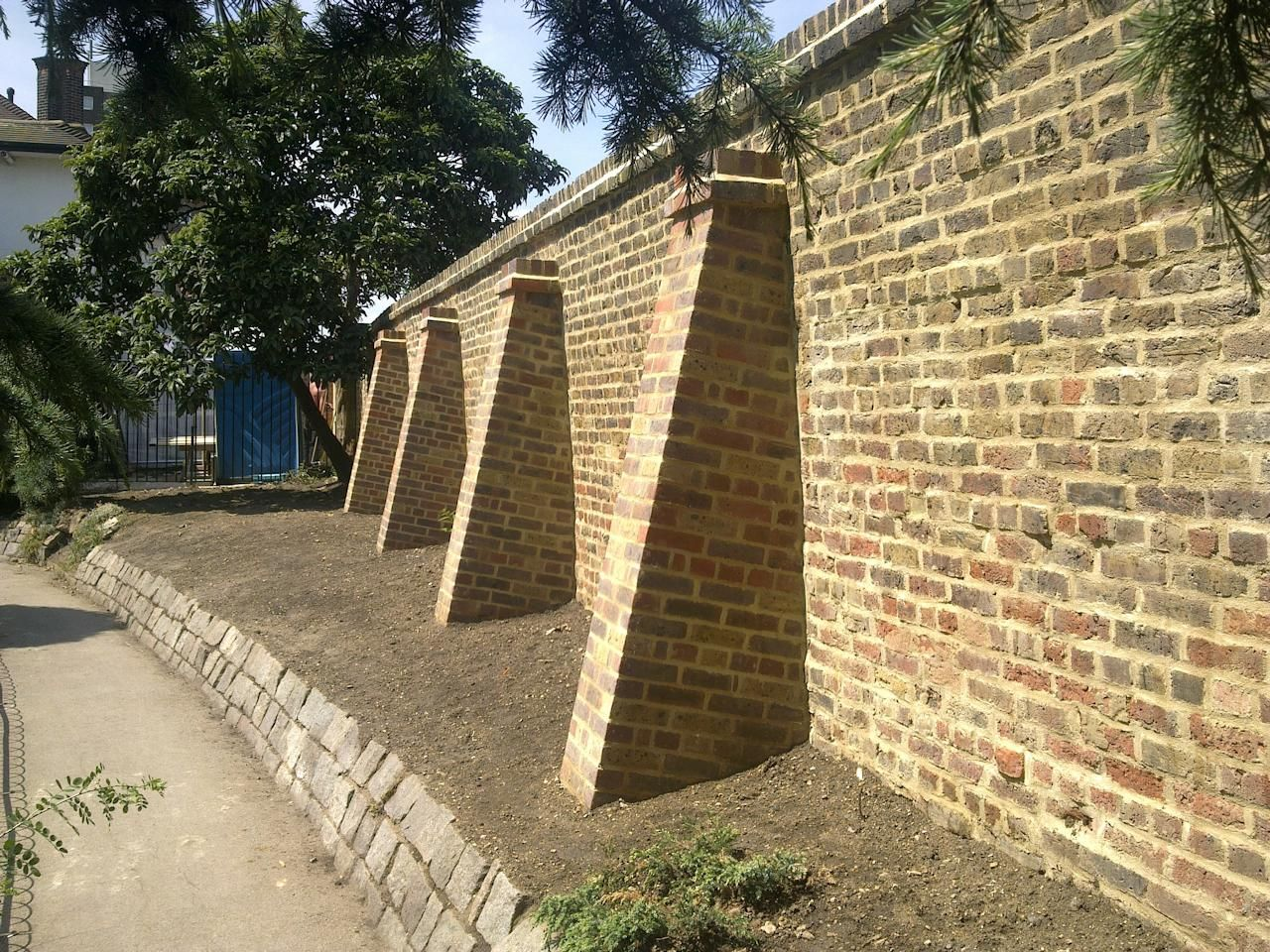 Brick buttress cappings google search earthbag home for Brick garden wall designs homes