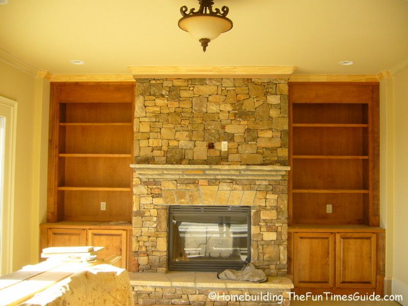 Built in bookshelves add a quality touch to custom homes for Bookshelves next to fireplace