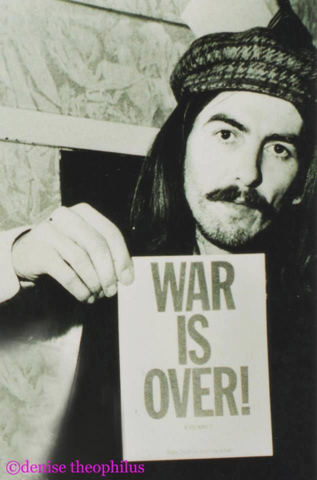 """George Harrison (holds promotional """"War Is Over"""" poster for the December 15, 1969 UNICEF benefit show he took part in with John & Yoko, and other artists at The Lyceum"""