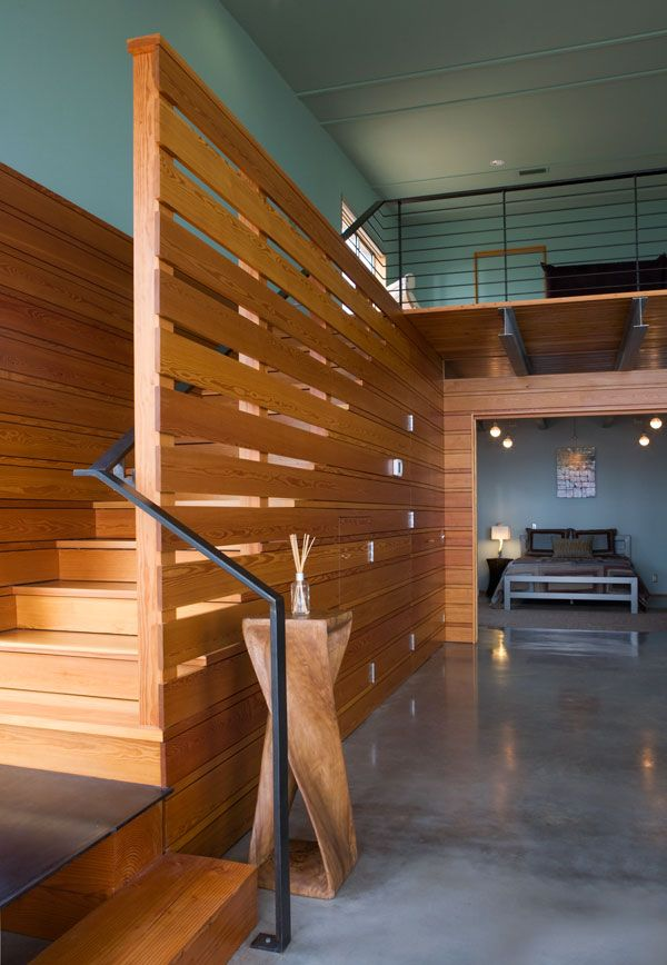interesting staircase design with partition walls lead to loft mezzanine area made from fir decking