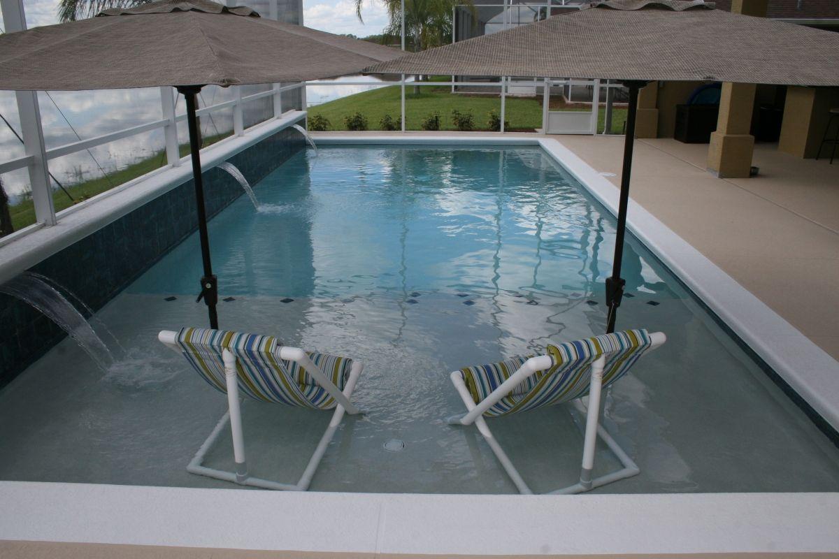 Rectangular linear pool with large sunshelf and umbrella inserts ...