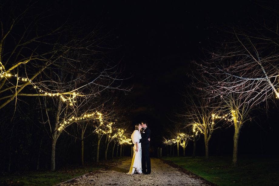 Bride and groom kiss under somerset starlight