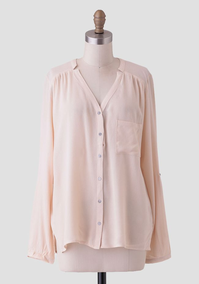 Designed with soft pleating at the shoulders and back for added interest, this oversized cream blouse features a button-up front with a single front pocket.