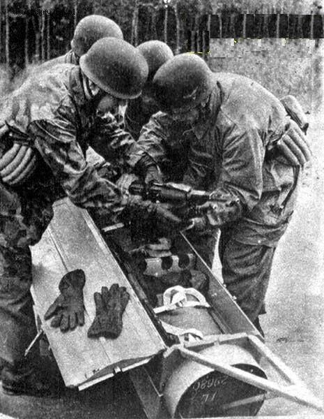 Fallschirmjäger (un)loading a weapons cannister. Note the Knee or elbow protecting pads at the belt.