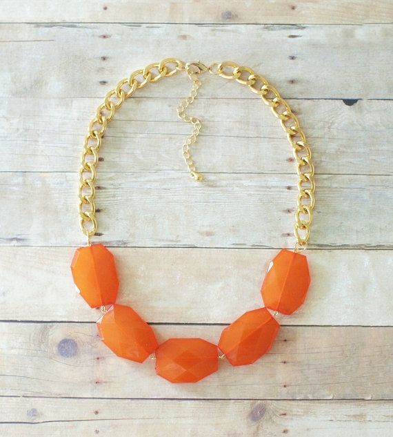 A single strand statement necklace featuring burnt orange faceted beads on chunky gold chain.    Add a bright pop of color to any outfit with this
