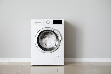 Modern washing machine with laundry near white wall , # ...