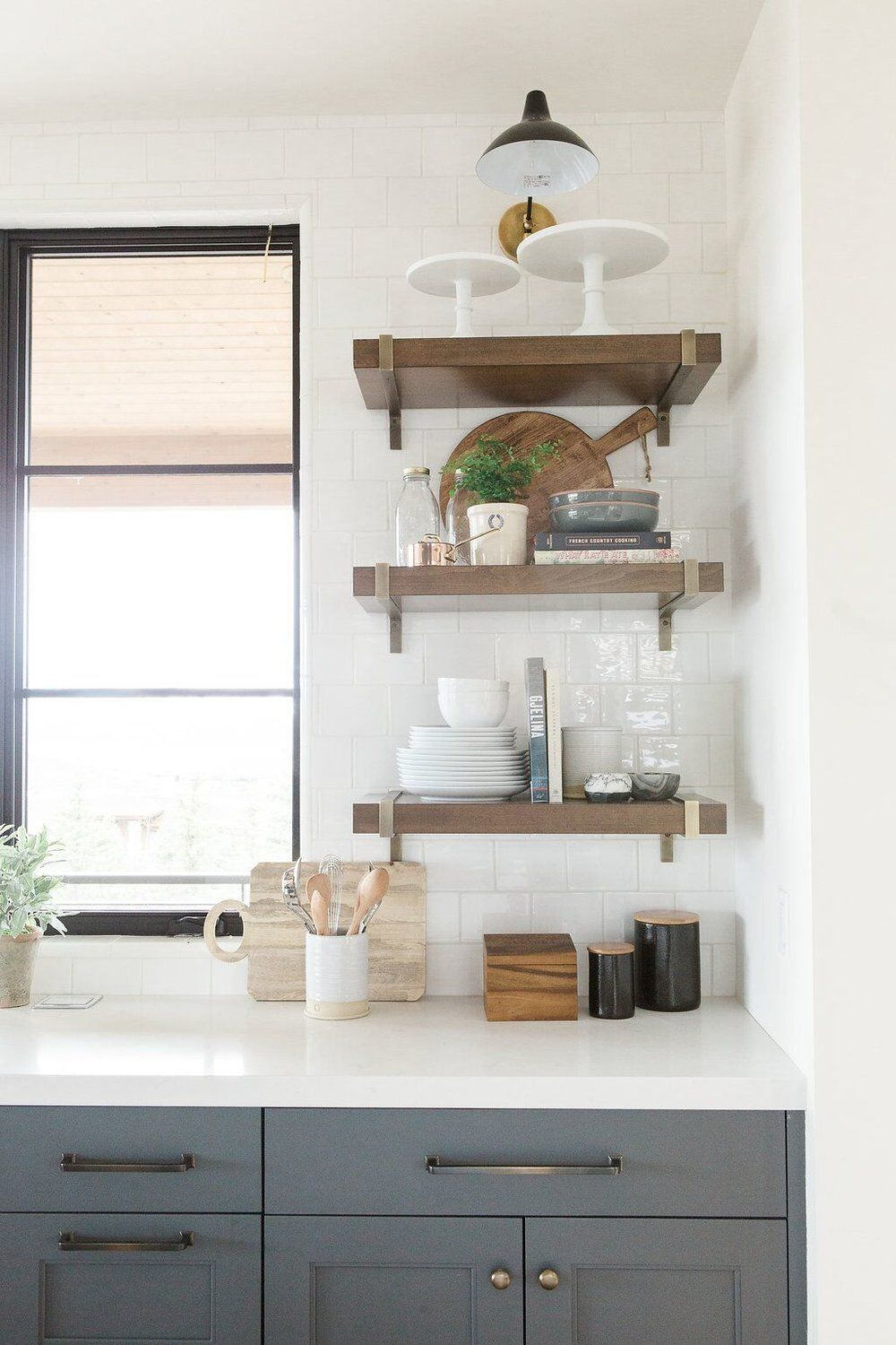 Modern kitchen with deep walnut open shelves white countertops and dark blue cabinets in benjamin moores cheating heart