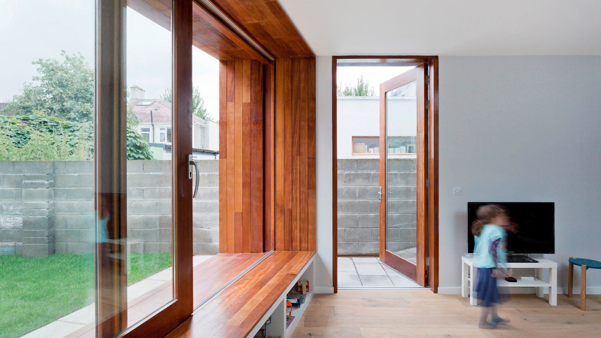 A Large Sliding Window Set Into The End Wall Of This Extension Is Enclosed Within Wooden Frame That Provides E For Internal And External Seating