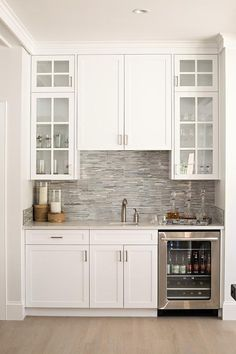 Built In Dining Room Wet Bar Features White Shaker Cabinets And A Glass Front Beverage Fridge Positioned Under Marble Countertop Accented With Gray Mosaic