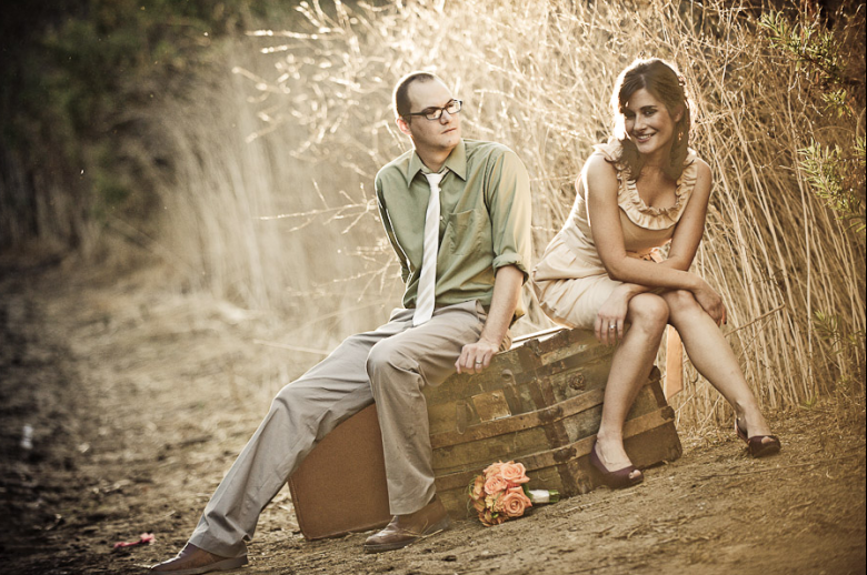 A couple pose together on a vintage rustic wooden trunk by a wheat field